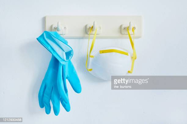still life of a face mask and protective gloves hanging at a coat hook - glove stock pictures, royalty-free photos & images