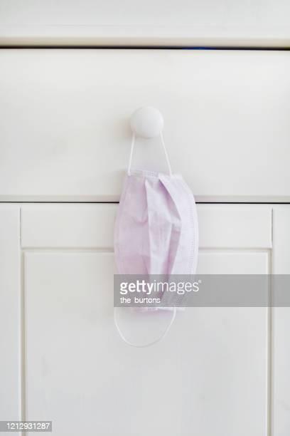 still life of a face mask hanging at a cabinet in bedroom - atemschutzmaske stock-fotos und bilder