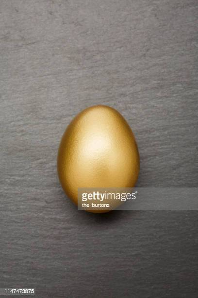 still life of a golden egg on dark gray background - ei stock-fotos und bilder
