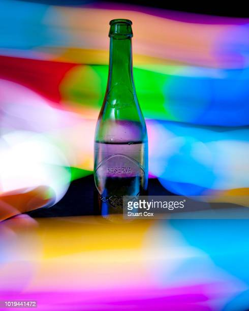 still life of a green glass bottle surrounded by multi-colored light painting effects. - bottle green stock pictures, royalty-free photos & images