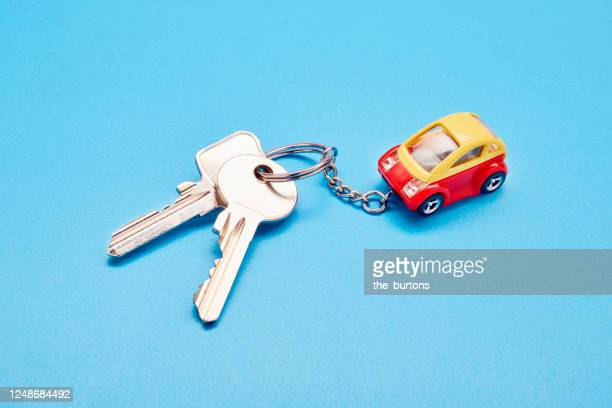 still life of a keyring with keys and a small toy car on blue background - oorhanger stockfoto's en -beelden