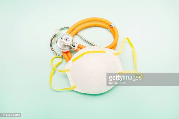 still life of a protective mask and stethoscope on turquoise background - atemschutzmaske stock-fotos und bilder