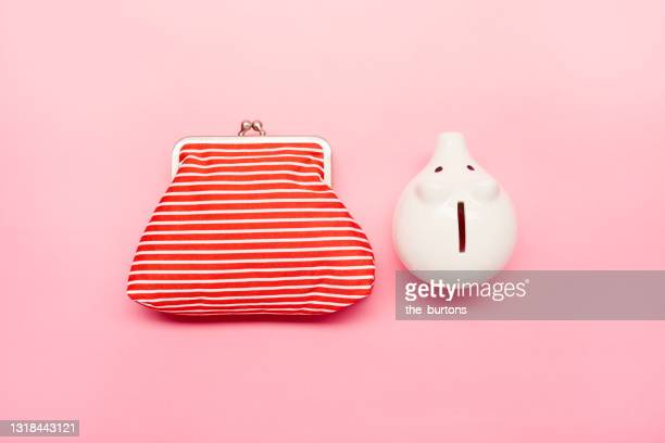still life of a red wallet and white piggy bank on pink background - pink purse stock pictures, royalty-free photos & images