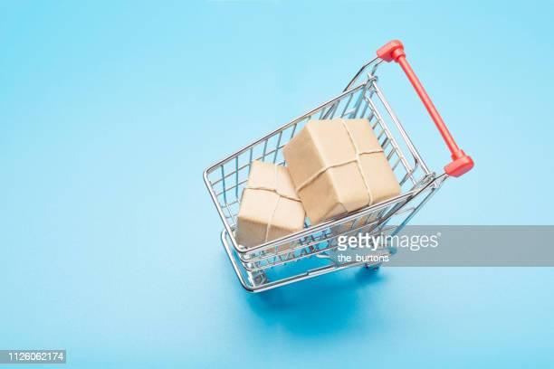 still life of a small shopping cart and parcels - market retail space stock photos and pictures