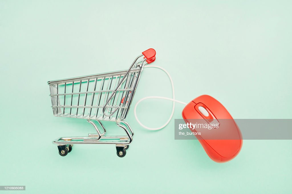 Still life of a small shopping cart and red computer mouse on turquoise background : Stock Photo