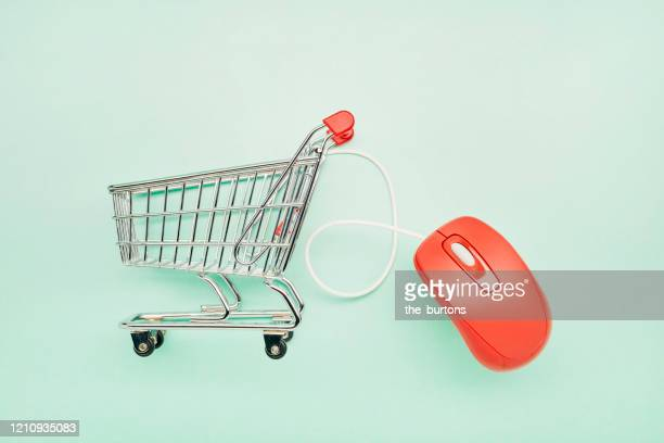 still life of a small shopping cart and red computer mouse on turquoise background - mercado espaço de venda no varejo - fotografias e filmes do acervo