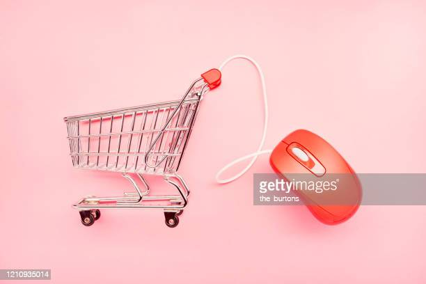 still life of a small shopping cart and red computer mouse on pink background, online shopping - internet stockfoto's en -beelden