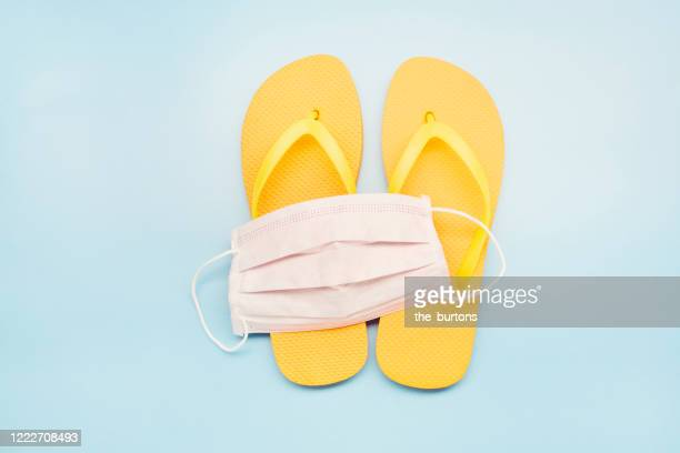 still life of a white face mask and orange flip-flops on blue background, on vacation with a protective face mask - travel stock-fotos und bilder