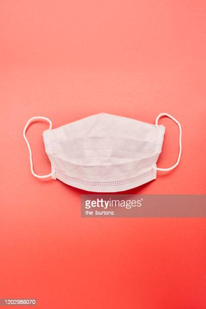 still life of a white face mask on red background - máscara quirúrgica fotografías e imágenes de stock