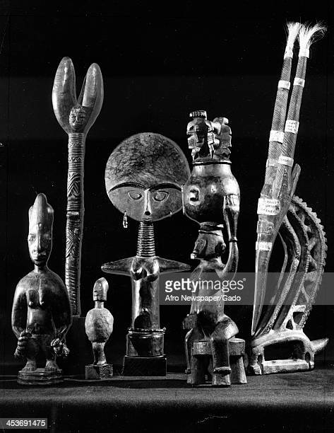 A still life of African art from Nigeria and the Ivory Coast including statues tribal masks and totems 1970
