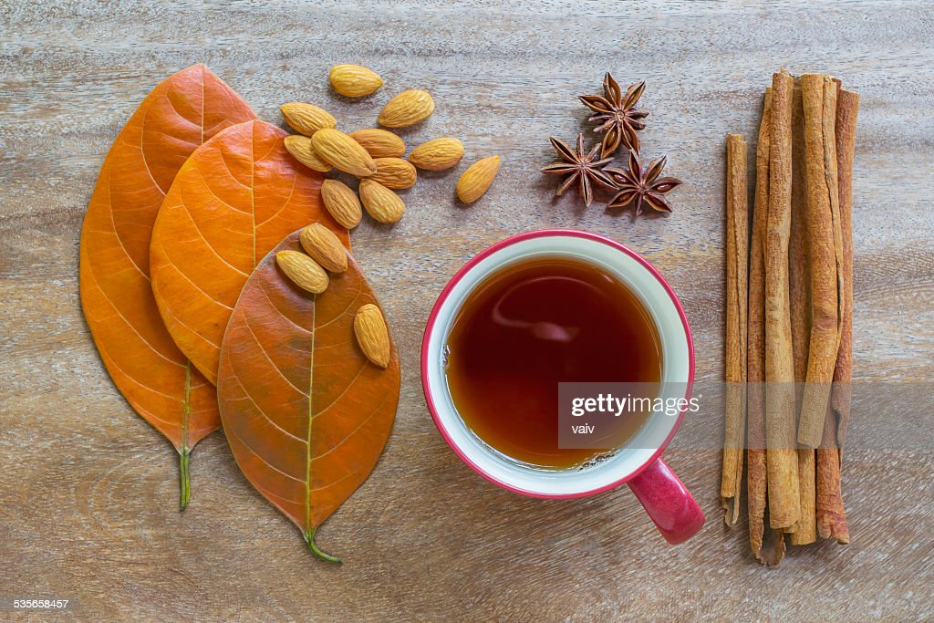 Still life of autumn leaves, almond seeds, cup of tea, anise cloves, and cinnamon sticks on wooden surface : Stock Photo