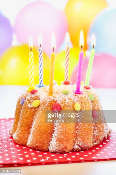 Still Life Of Birthday Cake With Candles Lit And Balloons