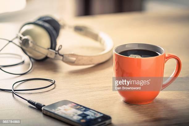 Still life of black coffee, headphones and smartphone