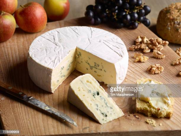 still life of blue brie with walnuts, grapes and apples on chopping board - brie stockfoto's en -beelden