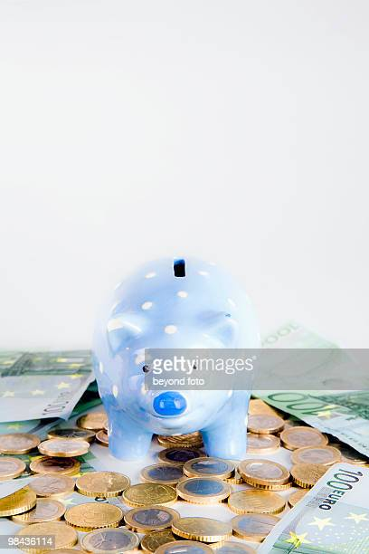 still life of blue piggybank with euro coins and banknotes
