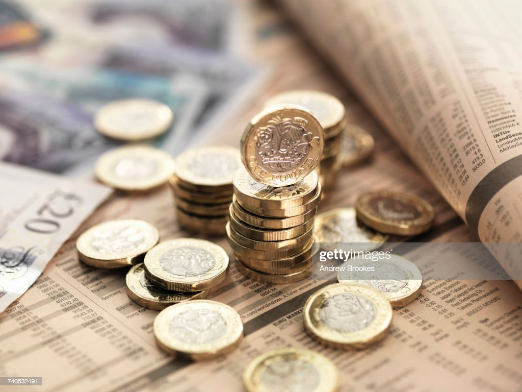 Still life of British currency on financial newspaper, close-up : Stock Photo
