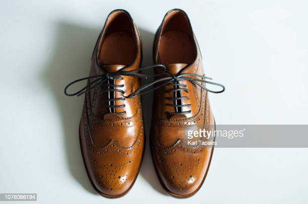 a still life of brown wingtip leather shoes - pair stock pictures, royalty-free photos & images