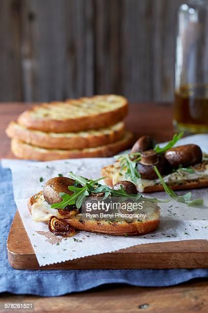 Still life of bruschetta with portobello mushroom roasted cipollini onion, gouda cheese and fresh arugula