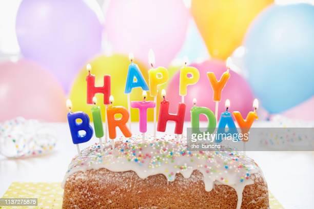 still life of cake with happy birthday candles lit and balloons - birthday balloons - fotografias e filmes do acervo