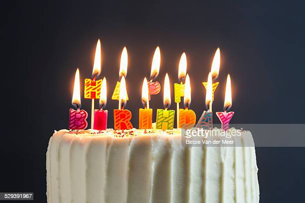 still life of cake with happy birthday candles. - birthday cake stock photos and pictures
