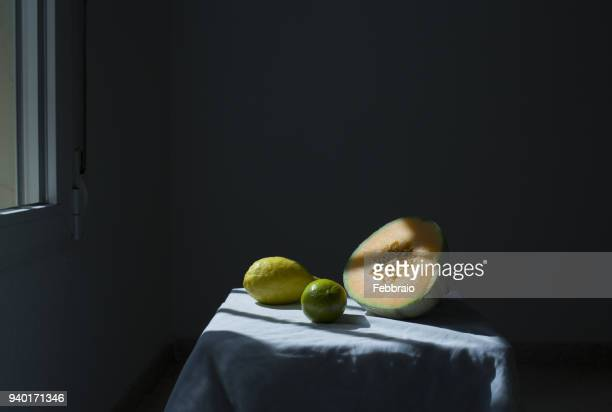 Still life of cantaloup, lime and lemon in shady light coming from a window
