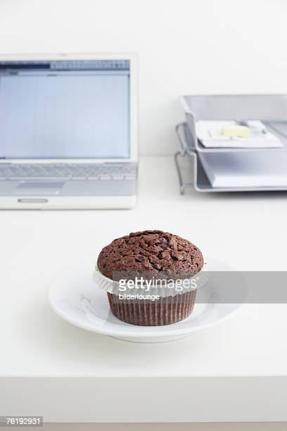 still life of chocolate muffin on plate on office desk