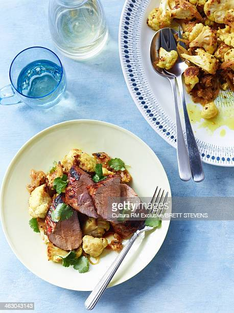 Still life of citrus and chilli pork with cauliflower