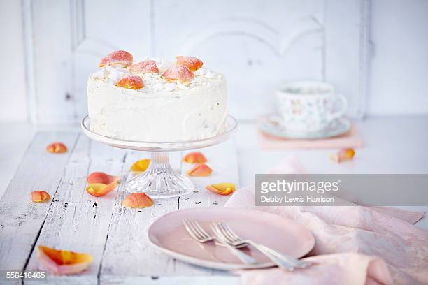 Still life of cream cake on cake stand garnished with rose petals