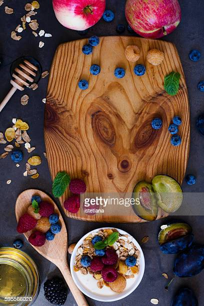 Still life of cutting board surrounded by fresh fruits and berries and bowl of breakfast muesli with  wheat flakes, blueberries, rasberries, top view