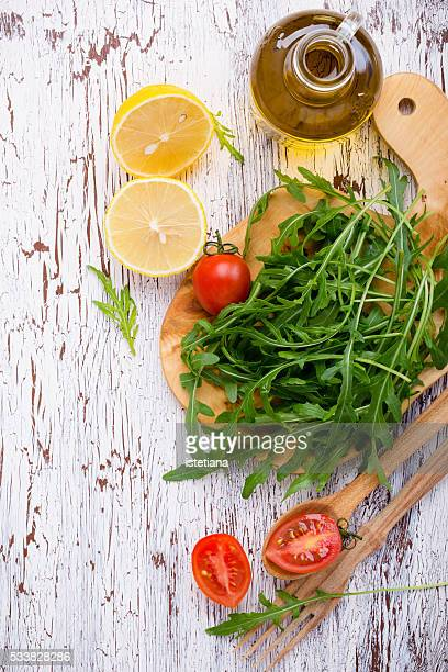 Still life of cutting board, wooden spoon and fork with fresh raw salad ingredients on rustic wooden   table
