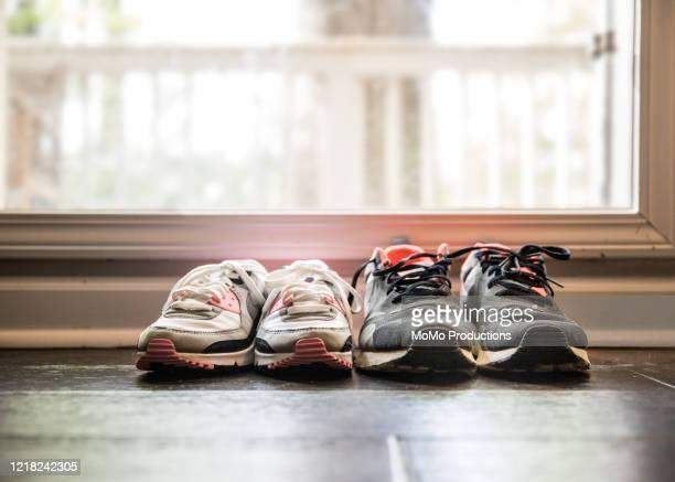 still life of different size shoes on floor at home - sportschuh stock-fotos und bilder