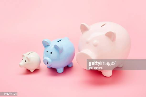 still life of differently sized white, blue and pink piggy banks in ascending size order on pink background - small group of objects stock pictures, royalty-free photos & images