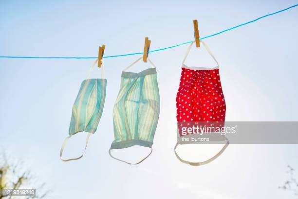 still life of face masks hanging at clothesline against clear sky and sun, diy sewing project - coronavirus stock-fotos und bilder
