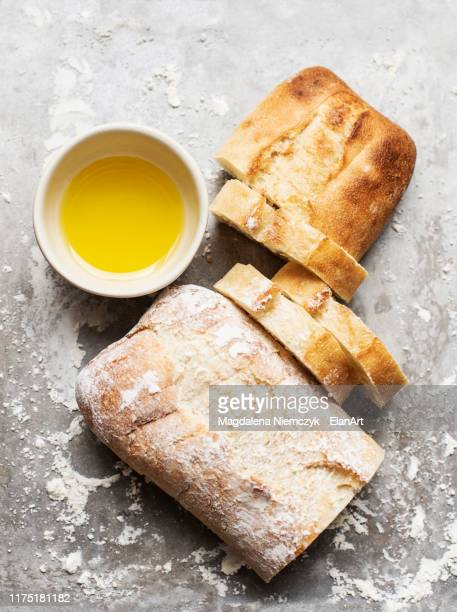 still life of floured and unfloured ciabatta loaf on baking tray with bowl of olive oil, overhead view - baking bread stock pictures, royalty-free photos & images