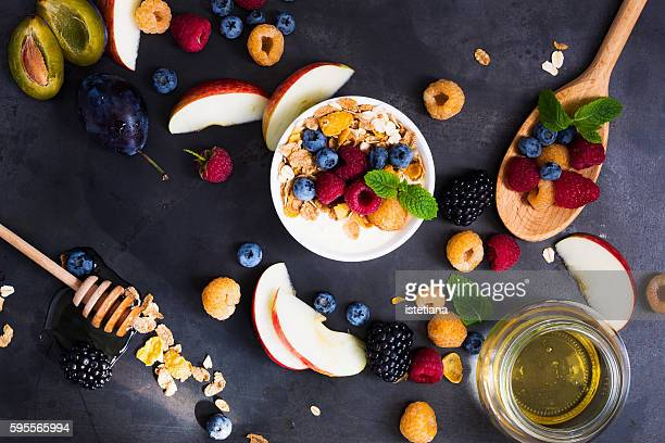Still life of  fresh fruits and berries and bowl of breakfast muesli with flakes, blueberries, rasberries, top view