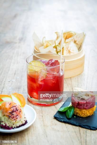 Still life of Giulietta cocktail with apple chips, steak tartare on a toast, foie gras, mango, wasabi sesame and chickpeas hummus, smoked salmon,...