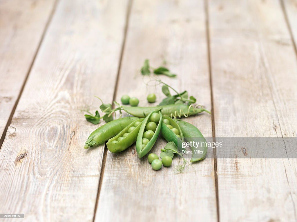 Still life of green peas in pods with pea shoots on wooden table : Stock Photo