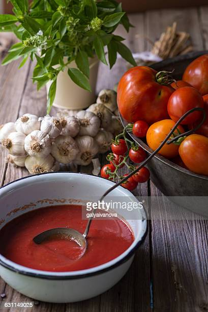 Still life of homemade tomato sauce with tomatoes, garlic and herbs