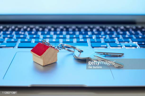 still life of key ring with a small house and keys on laptop computer - real estate stock pictures, royalty-free photos & images