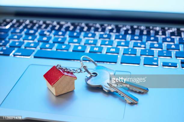 Still life of key ring with a small house and keys on laptop computer