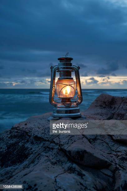 still life of lantern standing on rocks by the sea - lantern stock photos and pictures