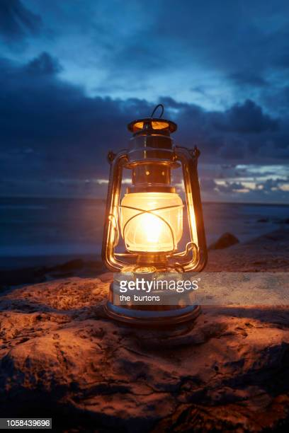 still life of lantern standing on rocks by the sea - dusk dark photos et images de collection