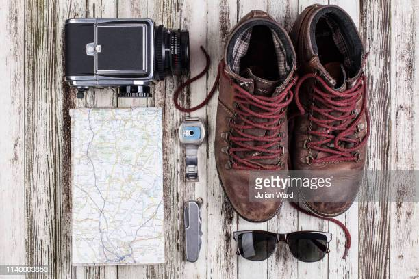 still life of map with medium format camera and hiking boots - hiking boot stock pictures, royalty-free photos & images