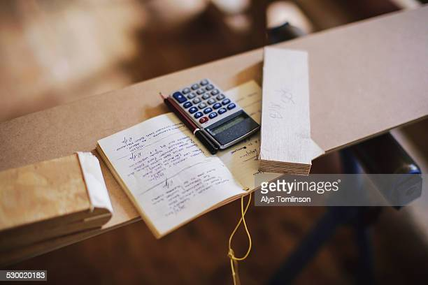 Still life of notebook and calculator in pipe organ workshop