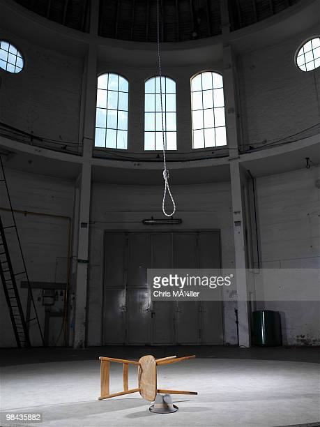 still life of overthrown chair hat and rope in empty building - hanging death photos stock pictures, royalty-free photos & images