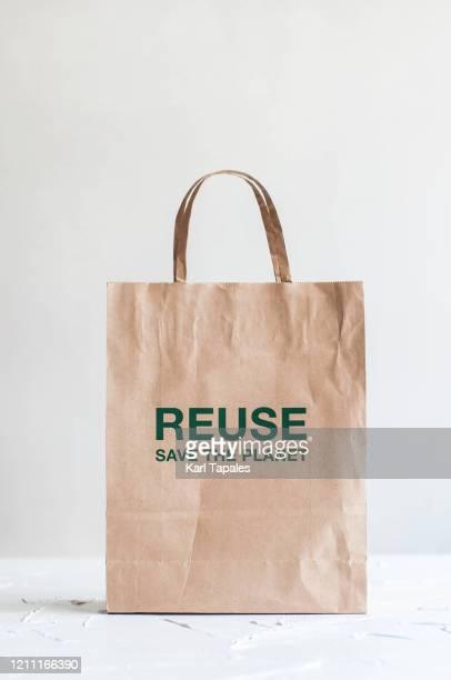 a still life of paper bag on a white background - bag photos et images de collection