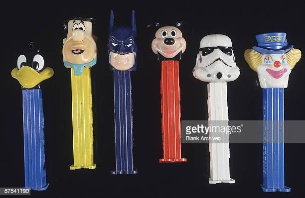 Still life of PEZ dispensers featuring the heads of popular cartoon characters Daffy Duck Fred Flintstone Batman Mickey Mouse Stormtrooper and Peter...