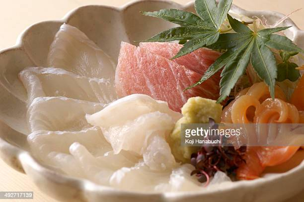 Still life of raw fish dish with leaves
