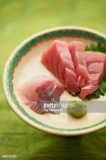 Still life of raw sliced fish dish with leaves