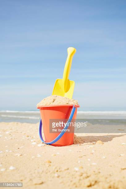 still life of red bucket and yellow shovel on the beach against sky - bucket stock pictures, royalty-free photos & images